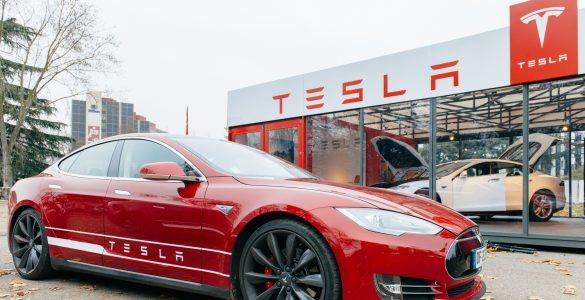 Tesla Modell vor einem Tesla Autohaus