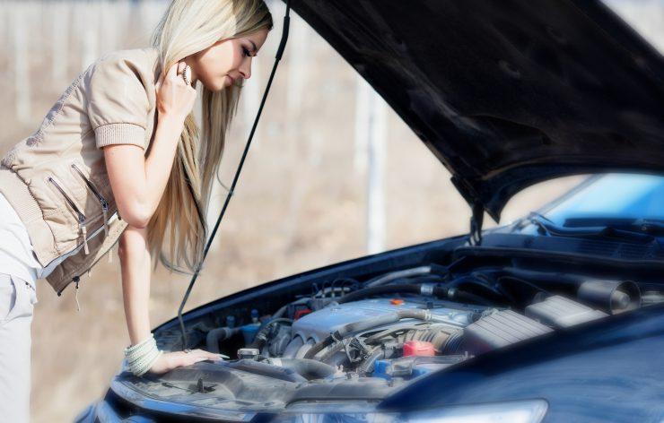 Frau überprüft den Motorraum