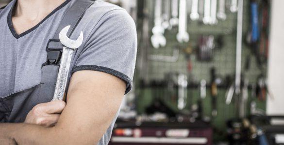 Mann mit Schraubenschlüssel in der Werkstatt