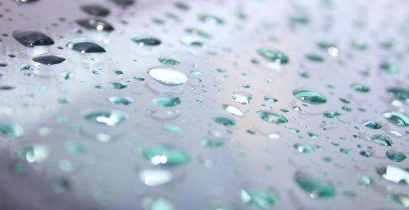 Regentropfen auf einer Windschutzscheibe, Nahaufnahme