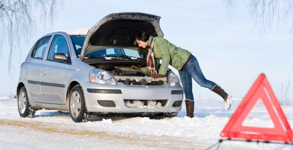 Autopanne im Winter, Warndreieck im Vordergrund