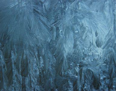 Eis und Eiskristalle an einer vereisten Autoscheibe