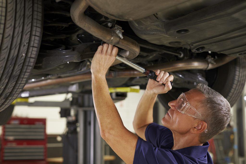 Mechaniker in einer Werkstatt arbeitet an einer Auspuffanlage unter einem Auto