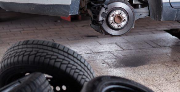 Reifen liegen vor einem Auto beim Wechsel