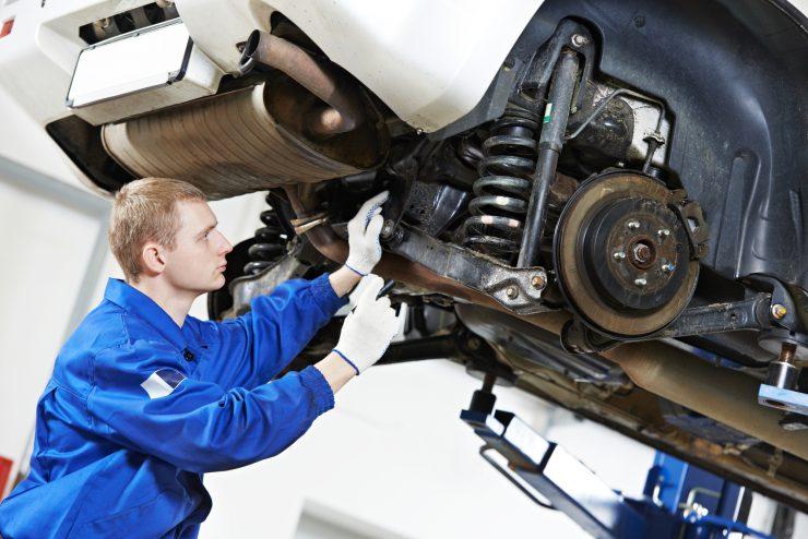 Werkstattmechaniker schaut sich aufgebocktes Auto von unten an.