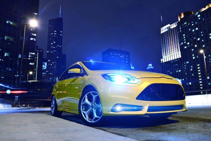 Beleuchtetes gelbes Auto mit Xenonscheinwerfer in einer Großstadt