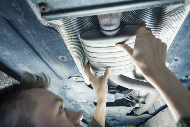 Mechaniker arbeitet an der Abgasanlage unter einem Auto mit Werkzeug