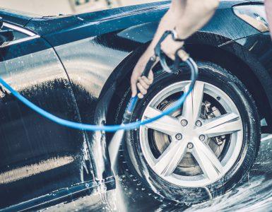 Auto wird mit einem Dampfstrahler von Hand gewaschen, Nahaufnahme auf Kotflügel und Rad, Autowäsche zuhause