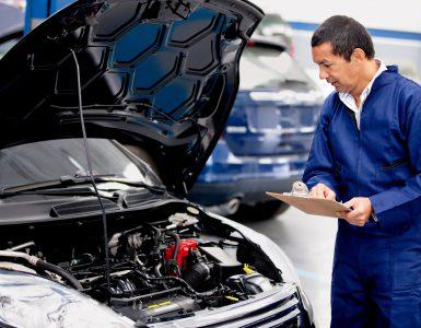 Mechaniker schaut in Motorinnenraum und macht Notitzen