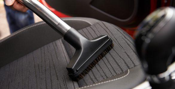 Mann saugt Fahrersitz eines Fahrzeuges.